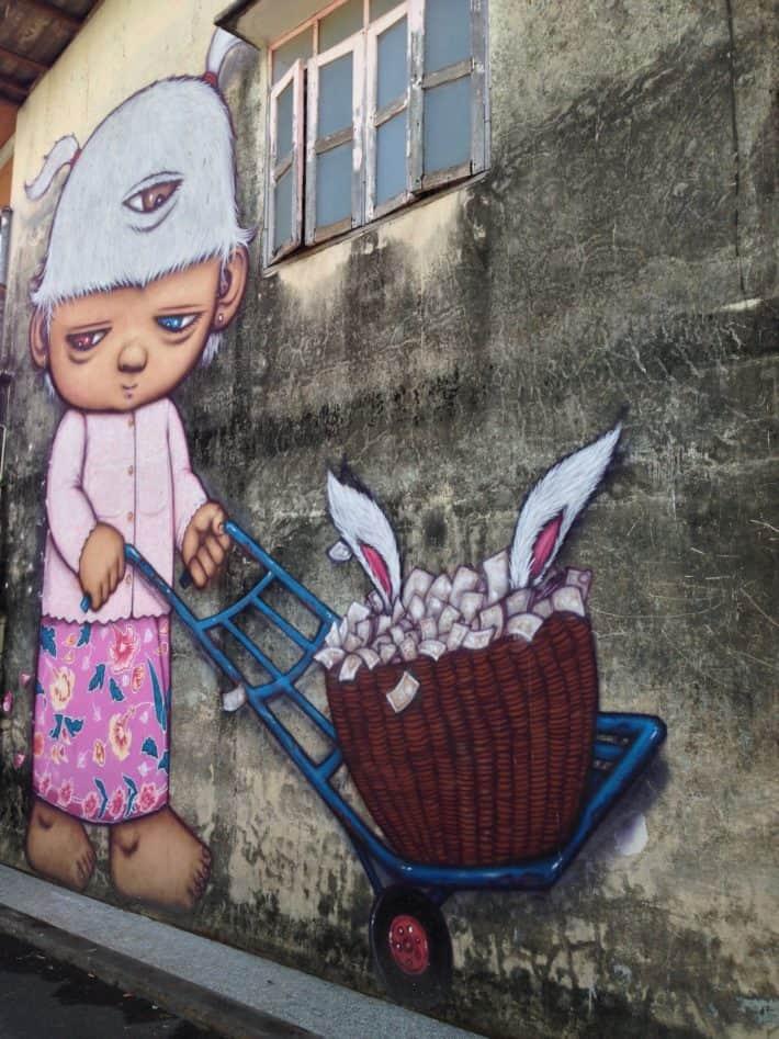 Streetart in Puhket Town, Thailand, Niedliche Figur, Schubkarre, Hasenohren an Hauswand