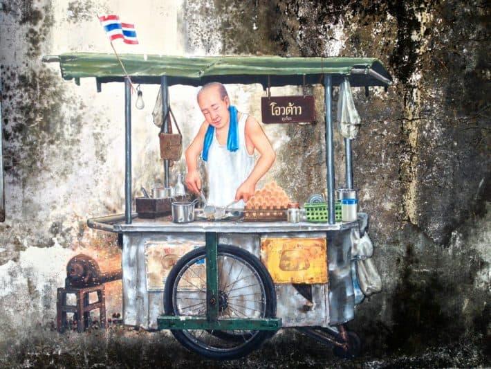 Streetart in Phuket Old Town, Thailand, Mann an Garküche bereitet Essen zu
