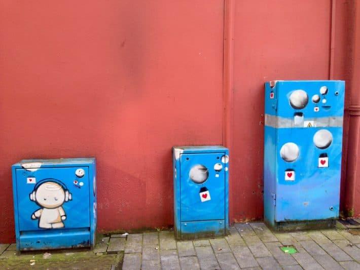 Streetart Irland Juni 2017 Limerich, rote Wand, blaue Strom- und Versorgungskästen besprüht