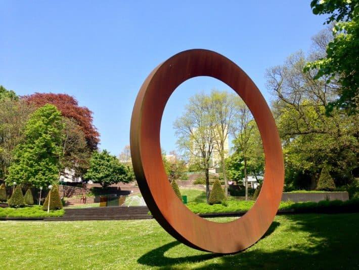 Sklupturengarten hinter dem Abteiberg Museum in Mönchengladbach, rostiger Stahlring, Blick auf das Museum, Bäume, Blauer Himmel