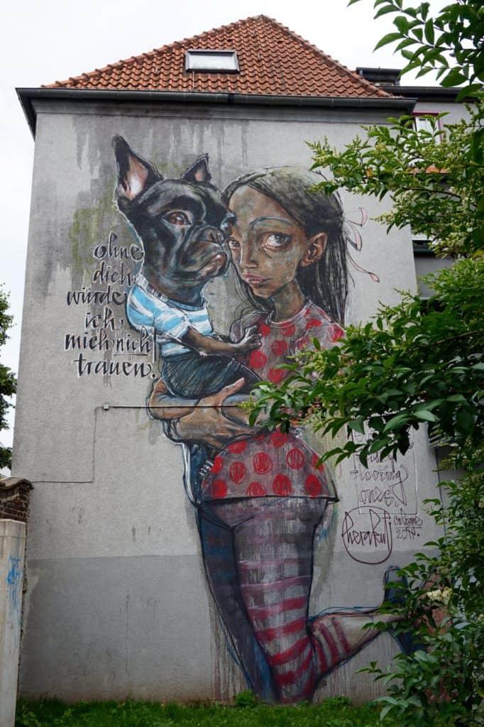 Streetart Juli 2017, Köln, komplette Fassade, Ehrenfeld, Frau mit Hund auf dem Arm