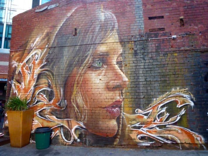 Streetart, langhaarige Frau auf Backsteinwand