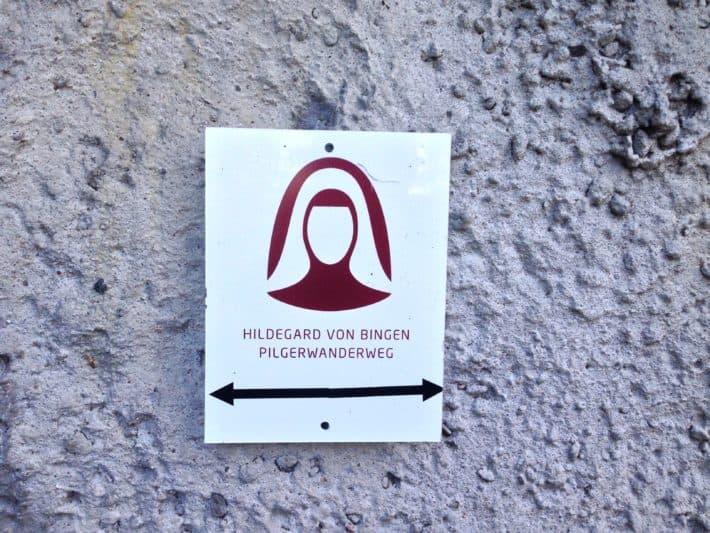 Wegweiser Hildegard von Bingen Pilgerwanderweg, weißer HIntergrund, bordeauxroter Nonnenkopf